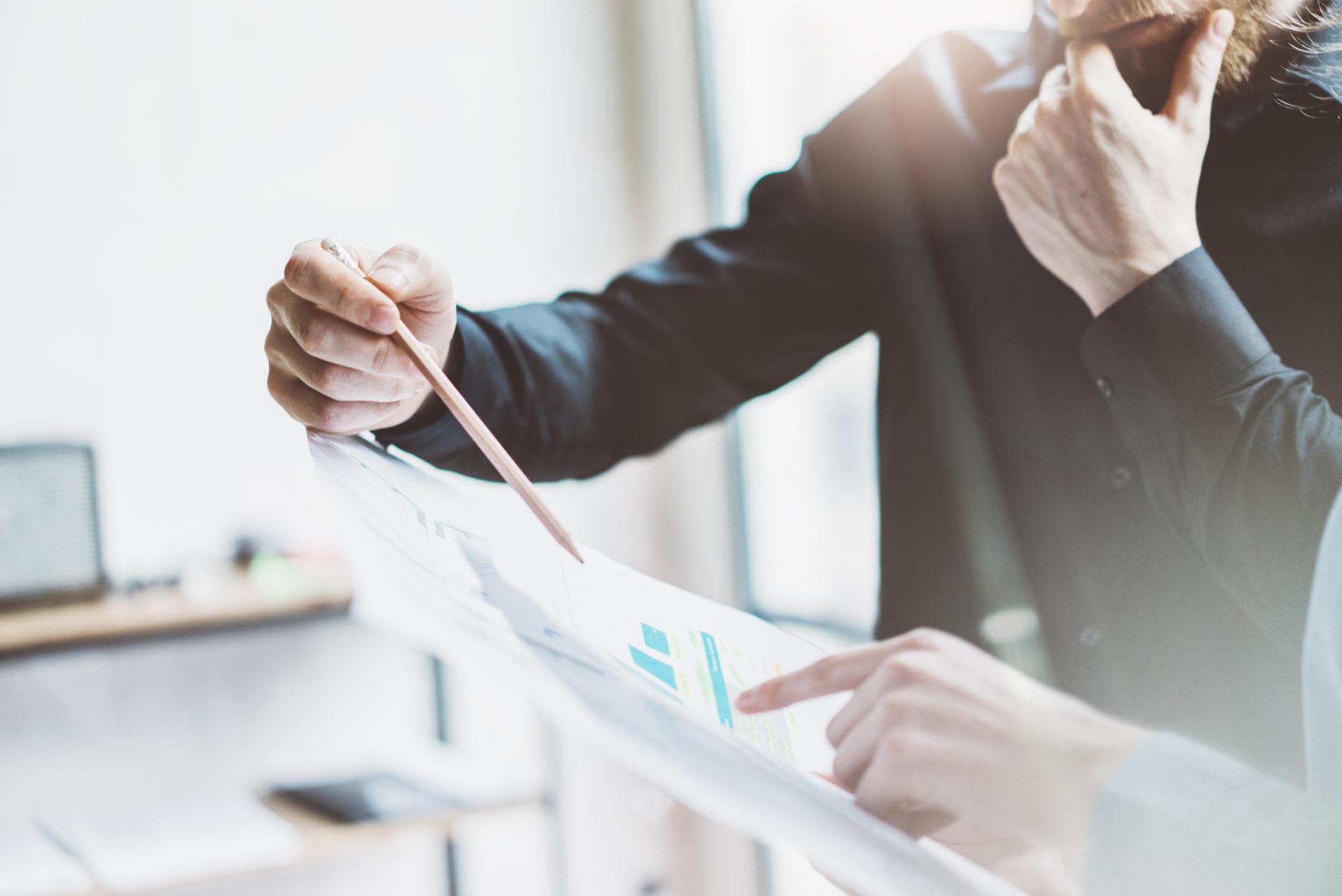 Ein Consultant bespricht mit einem Unternehmer einen Geschäftsplan oder Statistik