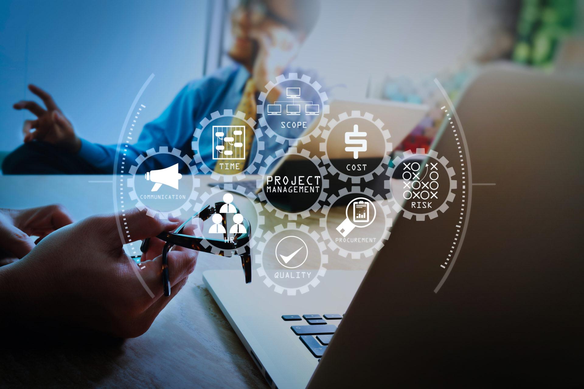 Darstellung einer Projektbesprechung und im Vordergrund Business Icons, Immotech übernimmt gesamtverantwortlich die Projektplanung und die Umsetzung