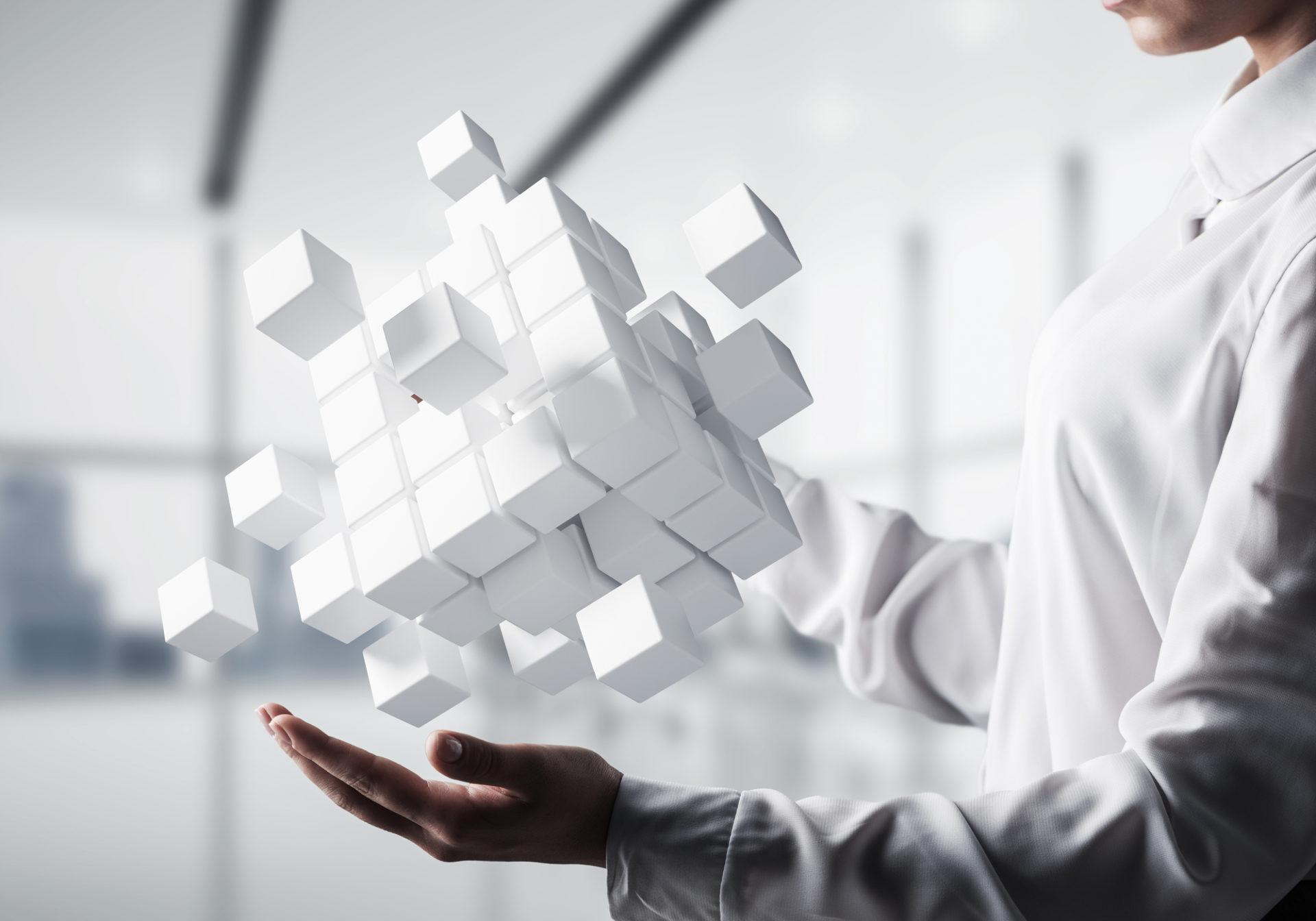 Darstellung für strategische Geschäftsentwicklung. Ein Mann kombiniert viele kleine Würfel zu einem Großen Ganzen.